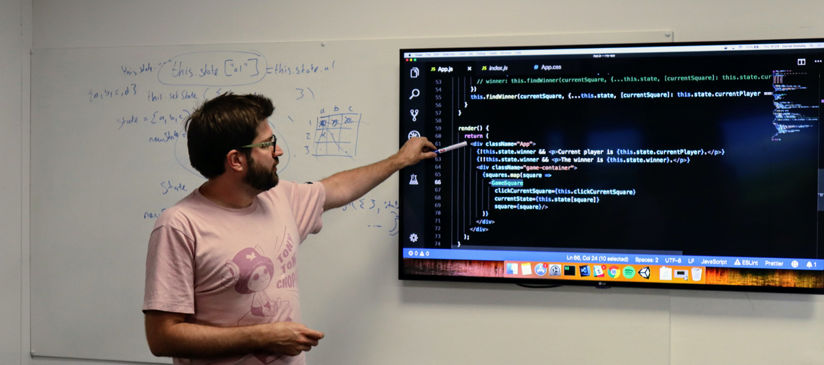 Dan Munday stands in front of a whiteboard and large screen teaching React, he is pointing at JavaScript code example