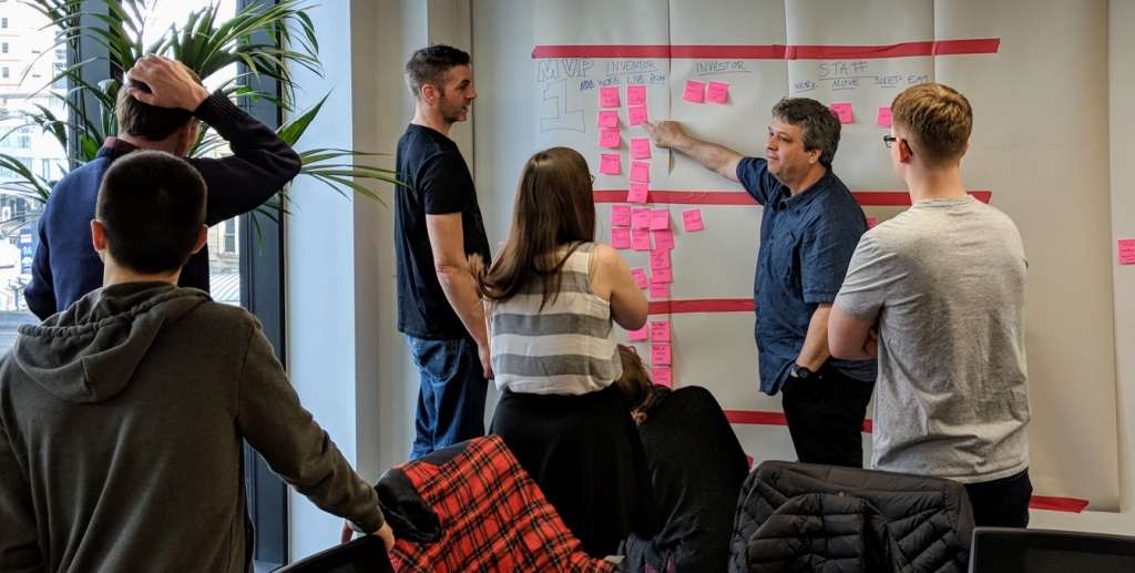 People discussing a project while moving sticky notes on the wall